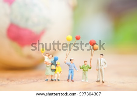 Miniature people, family and children with colorful balloons  standing in front of house. International Day of Families #597304307