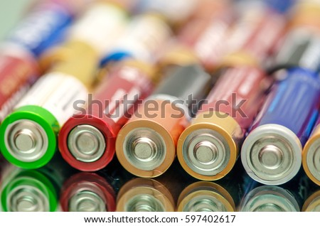 Closeup of pile of used alkaline batteries. Closeup colorful rows of selection of storage batteries energy background of colorful storage batteries. Alkaline battery aa size. Several batteries in rows #597402617