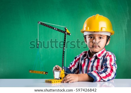 Cute little indian boy playing with toy crane wearing yellow construction hat or hard hat, childhood and education concept, isolated over green chalkboard