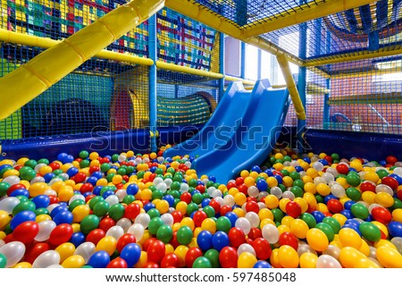 Modern children playground indoor. Inside the beautiful kids playground with a slide. Panoramic view of plastic dry pool with colorful balls for playing.  Royalty-Free Stock Photo #597485048