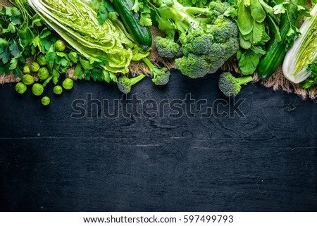 Collection of fresh green vegetables placed on black stone #597499793