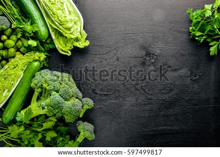 Collection of fresh green vegetables placed on black stone #597499817