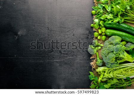 Collection of fresh green vegetables placed on black stone #597499823