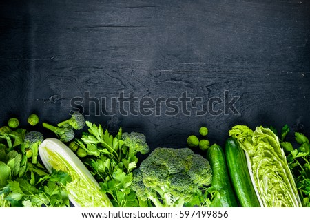Collection of fresh green vegetables placed on black stone #597499856