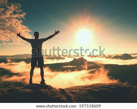 Happy man gesture of triumph with rams in air. Funny hiker on peak of sandstone rock in national park Saxony Switzerland watching to horizon Royalty-Free Stock Photo #597518609