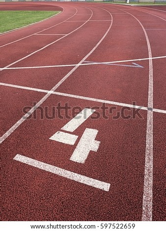 Number four. White track number on red rubber racetrack, texture of racetracks in small stadium #597522659