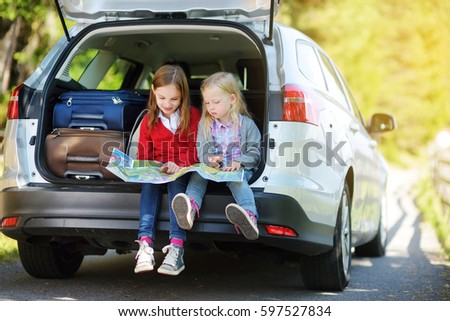 Two adorable little girls ready to go on vacations with their parents. Kids sitting in a car examining a map. Traveling by car with kids.  #597527834