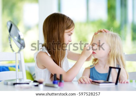 Two cute funny sisters applying make-up on sunny summer day at home. Adorable girls playing with their mommy`s cosmetic accessories.  #597528257