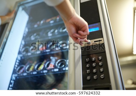 sell, technology and consumption concept - hand pushing button on vending machine operation panel Royalty-Free Stock Photo #597624332