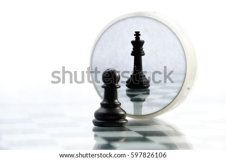 pawn pieces on the chessboard, the reflection in the mirror king, often in life things and people are not what they seem Royalty-Free Stock Photo #597826106