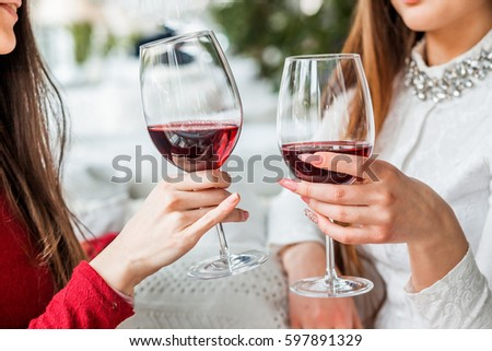 Two female friends drinking wine in restaurant #597891329
