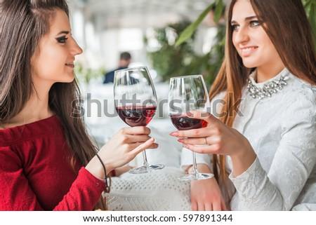 Two female friends drinking wine in restaurant #597891344