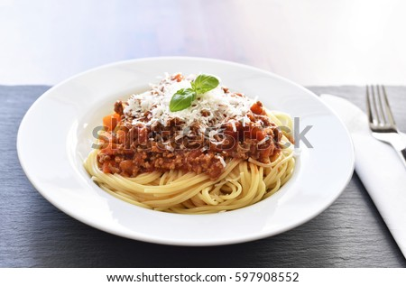 Spaghetti Bolognese on a white plate with decorative basil leaf. Italian cuisine, pasta with tomato sauce and parmesan cheese. #597908552