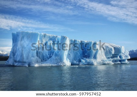 Single big blue iceberg in blue water in the center of the picture and blue sky with clouds on the background
