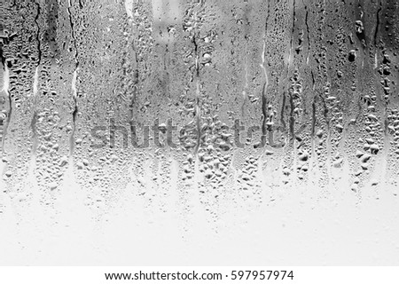 Black and white background of the condensate flowing water on the window glass Royalty-Free Stock Photo #597957974