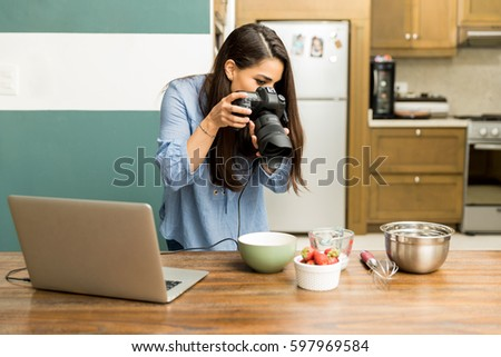 Pretty young woman working as a food photographer and taking some photos