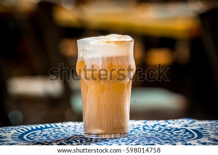 Ice coffee with milk on the wooden table in the bar #598014758