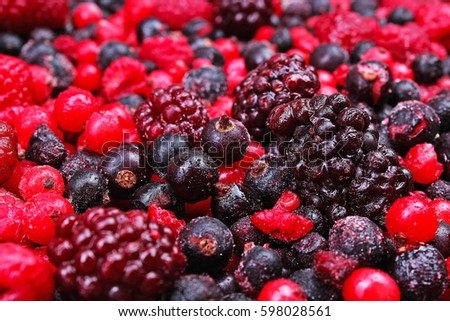 Frozen mixed berries as background. Blueberries,raspberries black berries and currant mulberry texture pattern.
