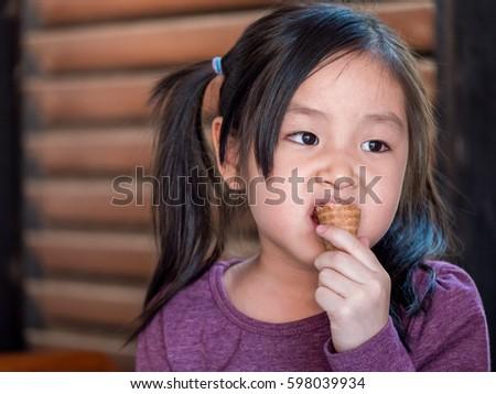 Little Asian girl eating ice cream, wood shade stripes background #598039934