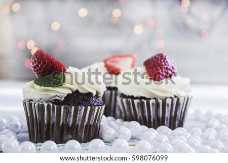 Chocolate cupcakes with white creme and strawberry on top #598076099