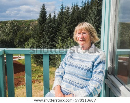 Senior woman relaxing at the house balcony. Serious woman is looking at view.  #598113689