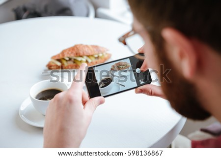Side view of a bearded man taking photo of his food in cafe