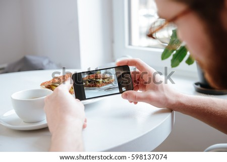Side view of a young bearded man taking photo of his food in cafe