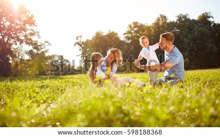 Happy male and female playing with children outside Royalty-Free Stock Photo #598188368