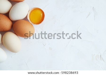 Fresh organic eggs and yolk on white table. Close up. Easter photo concept. Copyspace.  #598238693