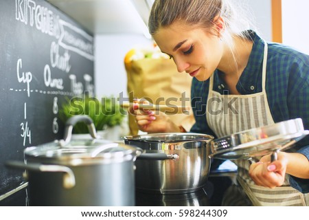 Young woman cooking in her kitchen standing near stove Royalty-Free Stock Photo #598244309