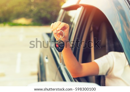 Used car and dealership concept. By woman's hand holding or giving a car key. Also for used car for sale concept, first car buy or purchase, sell, driver license, hire, loan, insurance and auction etc Royalty-Free Stock Photo #598300100
