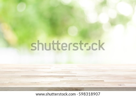 Wood table top on blur abstract natural green background - can be used for display or montage your products (foods)
