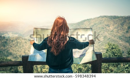 Travelers explore the mountainous forest map. Royalty-Free Stock Photo #598348394