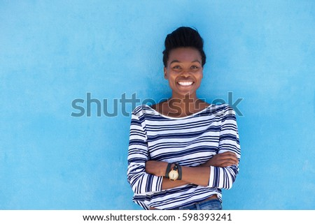 Portrait of young black woman smiling with arms crossed against blue background #598393241