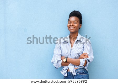 Portrait of african american woman smiling with arms crossed on blue background Royalty-Free Stock Photo #598395992