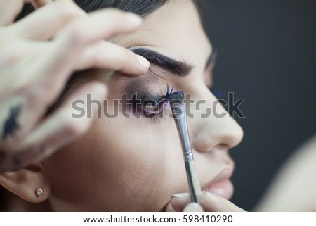 Young woman applying makeup to model in salon #598410290
