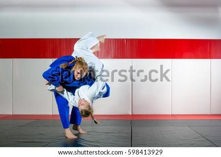 Two women fight judo on tatami Royalty-Free Stock Photo #598413929