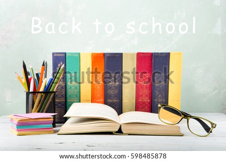 """A stack of color books, eyeglasses, stationery on a table and text """"Back to school"""" on green background #598485878"""