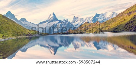 A magical panorama landscape with a lake in the mountains in the Swiss Alps, Europe. Wetterhorn, Schreckhorn, Finsteraarhorn et Bachsee. ( relaxation, harmony, anti-stress - concept).  #598507244