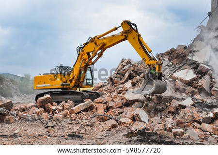 Excavator working at the demolition of an old industrial building. Royalty-Free Stock Photo #598577720