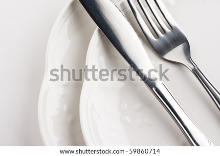 Close up of place setting with white plates, fork and knife. #59860714