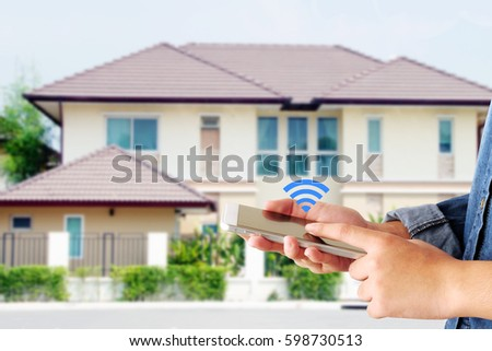 Hand holding smart phone over wifi icon and blur house background, smart home control concept #598730513