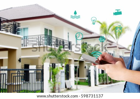 Hand using smart phone as smart home control application over blurred house background, smart home concept #598731137