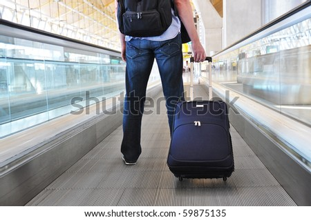 Traveler with a suitcase on the speedwalk #59875135