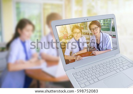 Modern white laptop computer with two female doctor with stethoscope, clipboard and Laptop on desk, doctor working in clinic on blurred background female doctor  working, insurance. concept #598752083