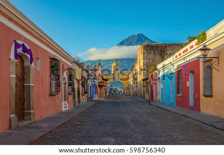 The main street of Antigua city with the yellow arch and the Agua volcano in the background during sunrise, Guatemala. #598756340