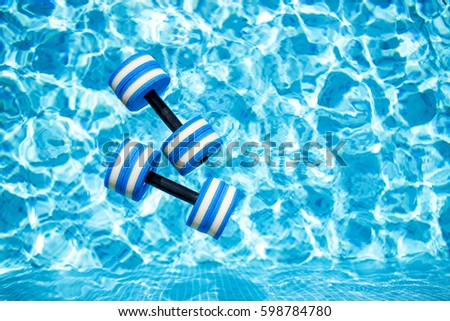 Top view of  plastic dumbbells for aqua aerobics  floating in blue water of swimming pool on summer day outdoors #598784780
