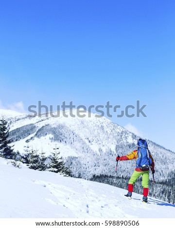 Winter hiking in the mountains on snowshoes with a backpack and tent. #598890506