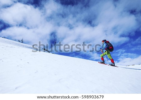 Winter hiking in the mountains on snowshoes with a backpack and tent. #598903679