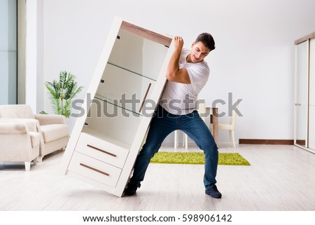 Young man moving furniture at home #598906142